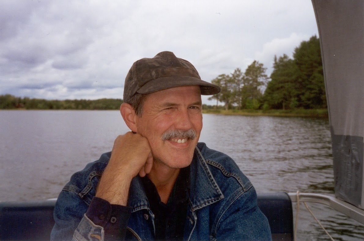 A picture of Keith riding on a pontoon boat and smilingsmiling